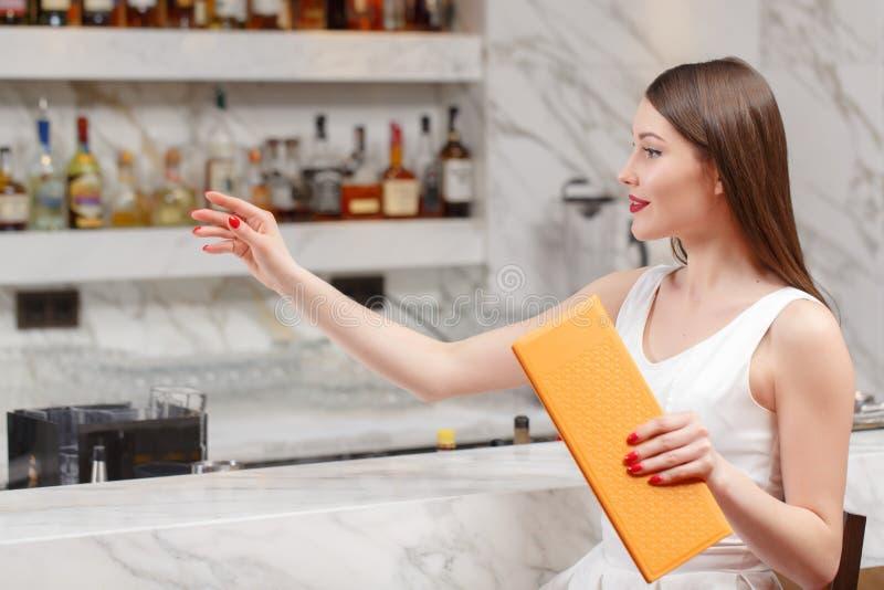 Kobieta trzyma menu przy barem obraz royalty free