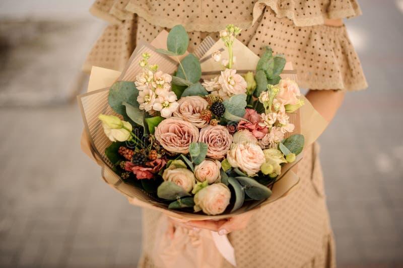 Kobieta trzyma nagiego barwionego bukiet kwiaty w beż sukni zdjęcia stock