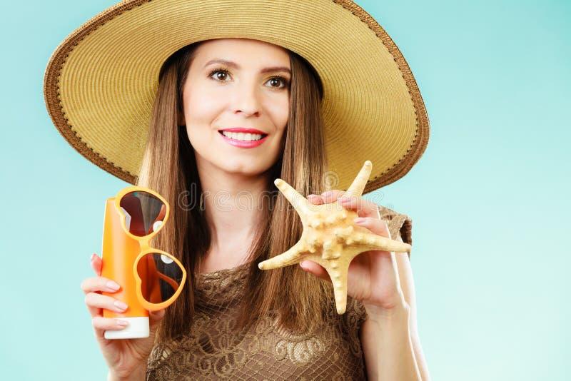Kobieta trzyma okulary przeciwsłonecznych i sunscreen płukankę obraz royalty free