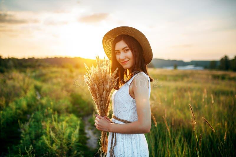 Kobieta trzyma pszenicznego bukiet w polu przy zmierzchem zdjęcie royalty free