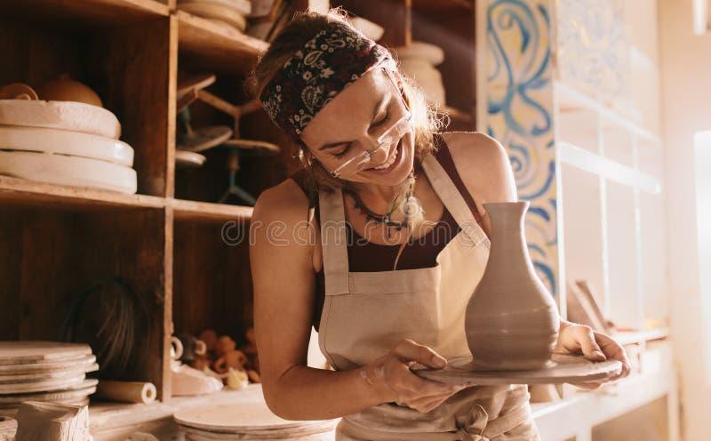 Kobieta trzyma skończonego glinianego garnek na garncarki koła bazie zdjęcie royalty free
