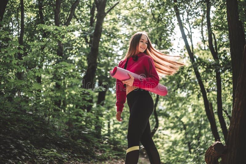 Kobieta trzyma sprawności fizycznej matę na trenować outdoors z trzepotliwym włosy w hoodie obrazy stock