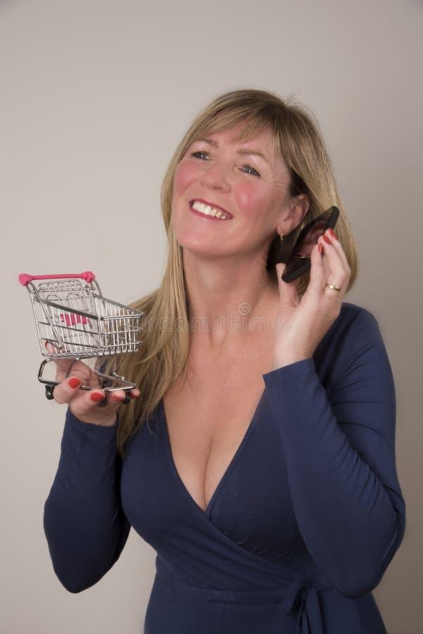 Kobieta trzyma supermarketa tramwaj z telefonem zdjęcia royalty free