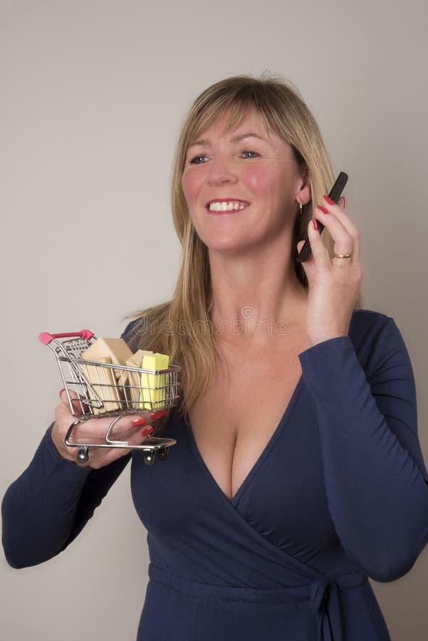Kobieta trzyma supermarketa tramwaj z telefonem zdjęcie stock