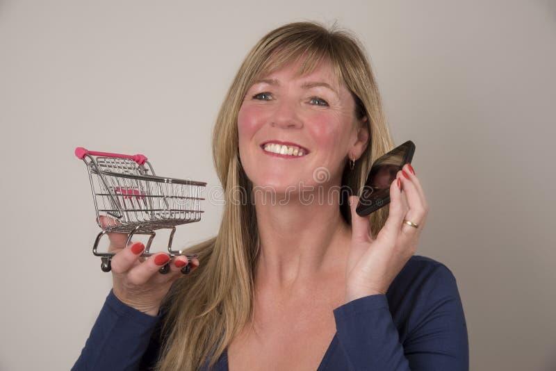 Kobieta trzyma supermarketa tramwaj z telefonem fotografia stock