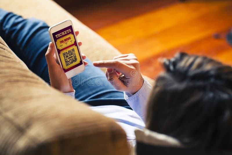 Kobieta trzyma telefon komórkowego kupować kinowych bilety zdjęcia stock