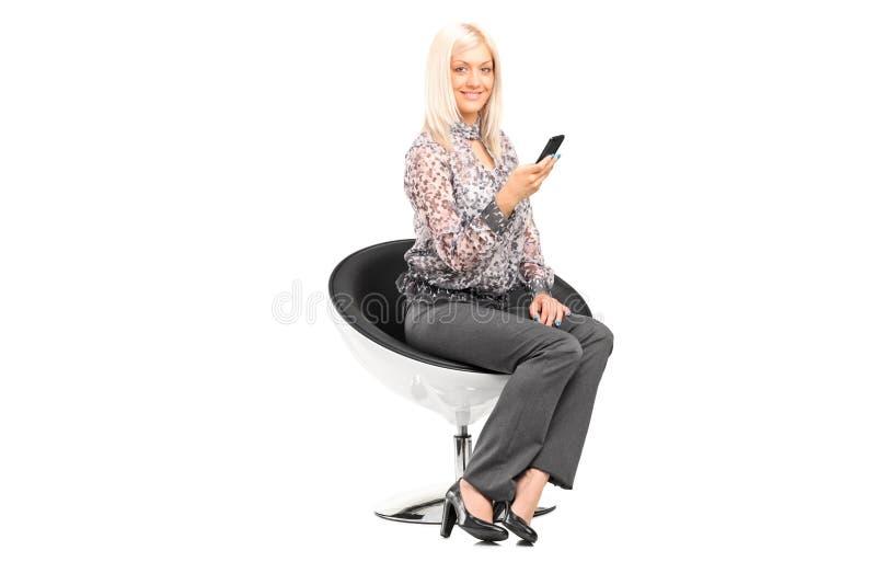 Kobieta trzyma telefon komórkowego sadzający w nowożytnym krześle zdjęcie stock