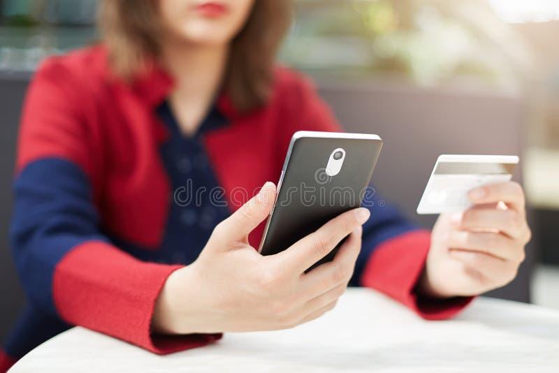 Kobieta trzyma telefon komórkowego w rękach płaci z kredytową kartą online w czerwieni ubraniach podczas gdy robić rozkazowi prze zdjęcia stock