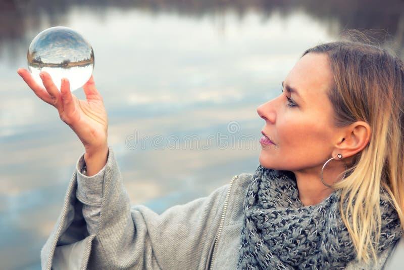 Kobieta trzyma up szklaną piłkę przed jeziorem zdjęcie stock