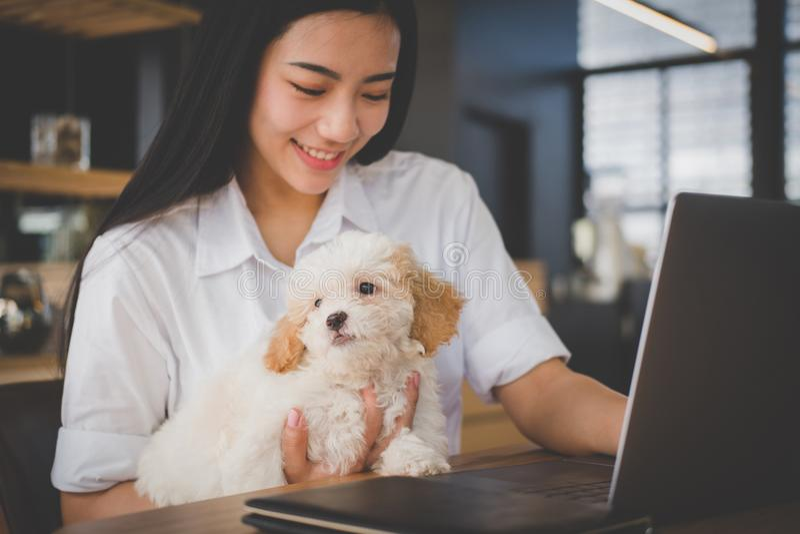 Kobieta trzyma uroczego psa przy cukiernianą restauracją żeński nastolatek s obraz royalty free