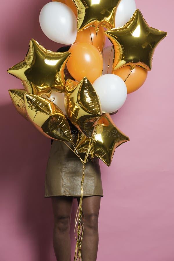 Kobieta trzyma wiązkę balony zakrywa twarz fotografia stock
