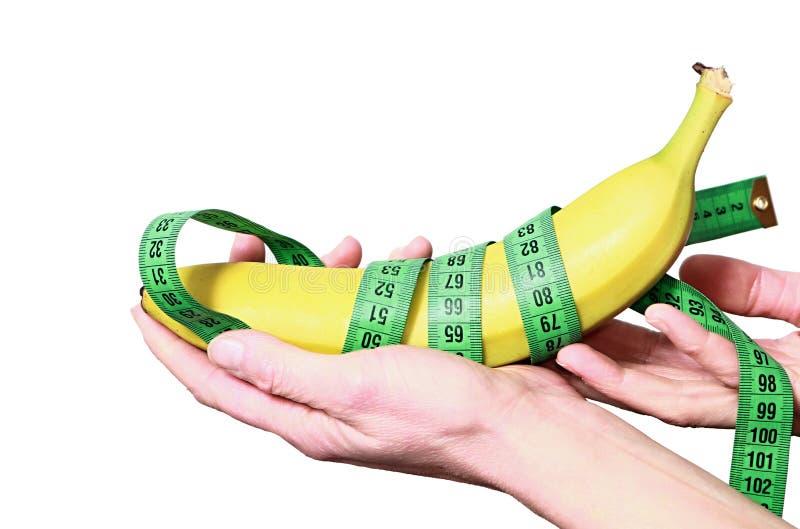 Kobieta trzyma zdrowego banana i taśmy miary obraz stock