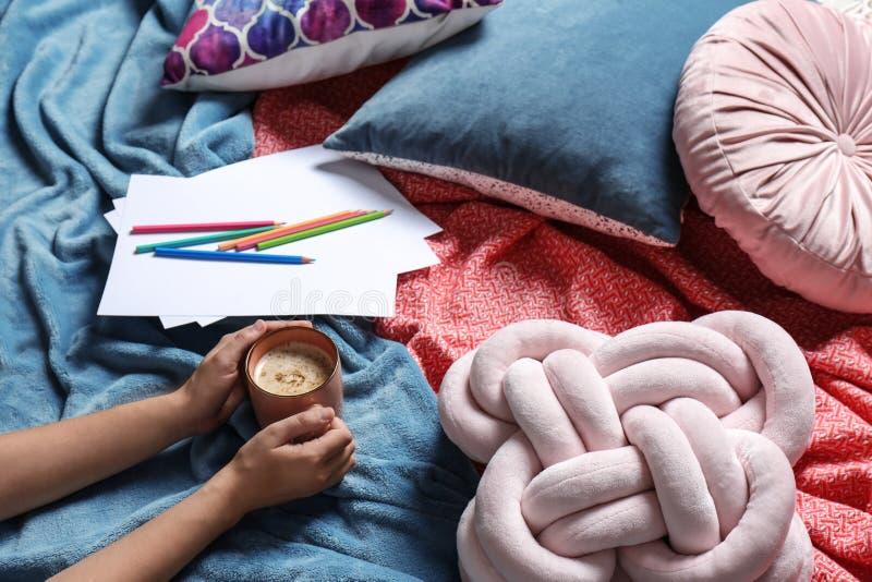 Kobieta trzymajÄ…ca filiżankÄ™ kawy leżąc na poduszkach i ciepÅ'ej plaży, zamkniÄ™ta zdjęcie royalty free