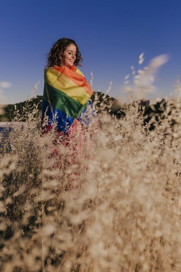 Kobieta trzymająca flagę Gay Rainbow o zachodzie słońca Szczęście, wolność i miłość dla par tej samej płci Styl zewnętrzny obrazy stock