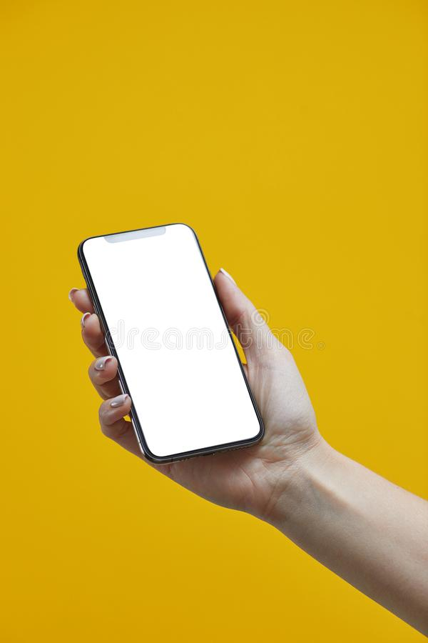 Kobieta trzymająca telefon komórkowy na żółtym tle z białym ekranem obraz stock
