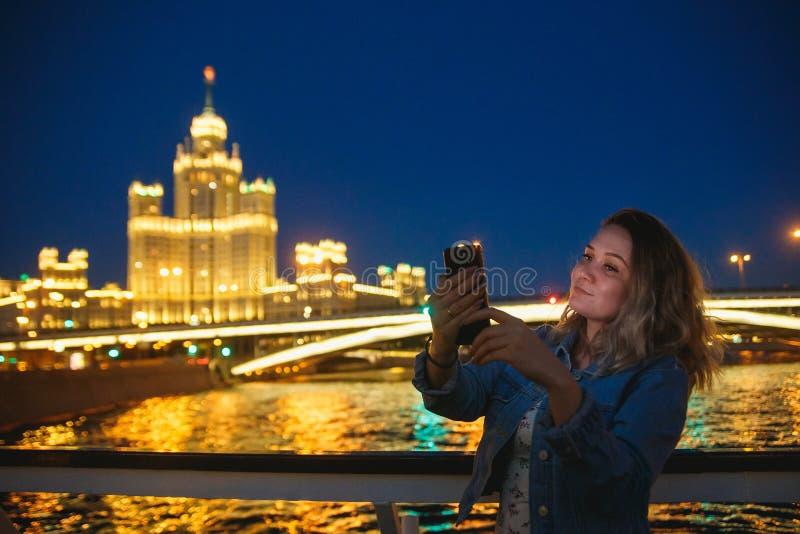 Kobieta turysta bierze obrazki na telefonie komórkowym podczas wycieczki w Moskwa Wiecz?r iluminacja Podr?? Rosja poj?cie obraz royalty free