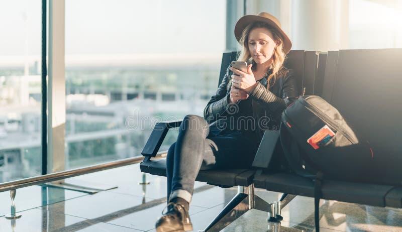 Kobieta turysta w kapeluszu, z plecakiem siedzi przy lotniskowym pobliskim okno, używa smartphone Modniś dziewczyny czekanie dla  zdjęcie royalty free