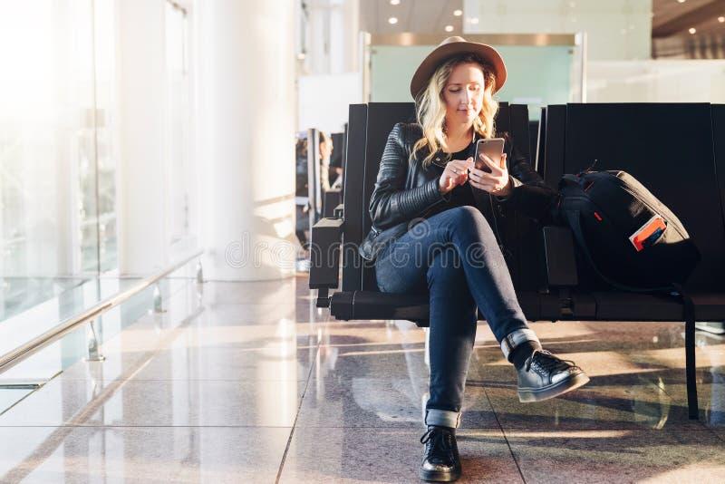 Kobieta turysta w kapeluszu, z plecakiem siedzi przy lotniskowym pobliskim okno, używa smartphone Modniś dziewczyny czekanie dla  obrazy royalty free