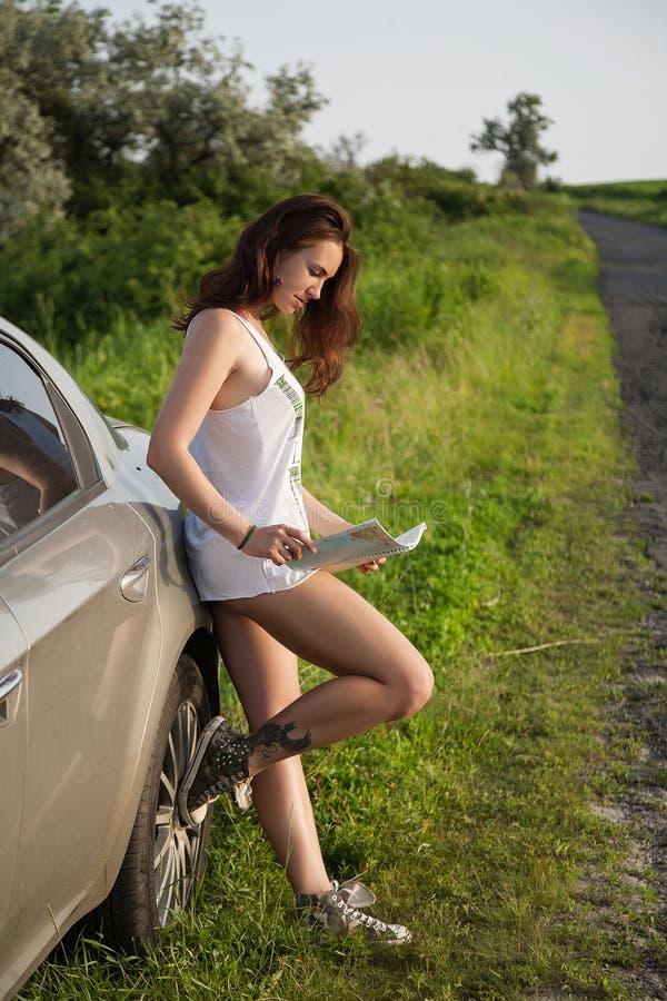 Kobieta turysta z mapą blisko samochodu fotografia royalty free