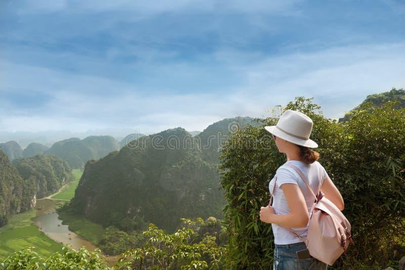 Kobieta turysta z plecakiem cieszy się dolinnego widok od wierzchołka góra fotografia royalty free