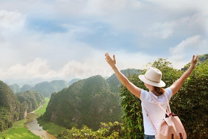 Kobieta turysta z plecakiem cieszy się dolinnego widok z rękami up od wierzchołka góra zdjęcia stock