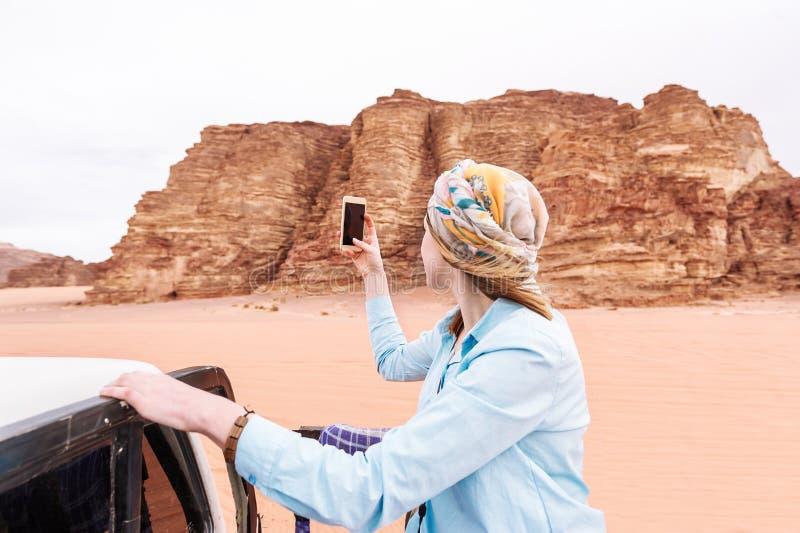 Kobieta turysty krótkopędy wideo lub fotografia na telefonie komórkowym jordańczyk pustynia zdjęcie stock