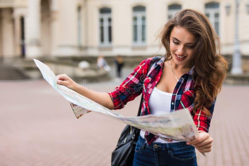 Kobieta turystyczna patrzejący mapę na ulicie podróży miasto obrazy royalty free