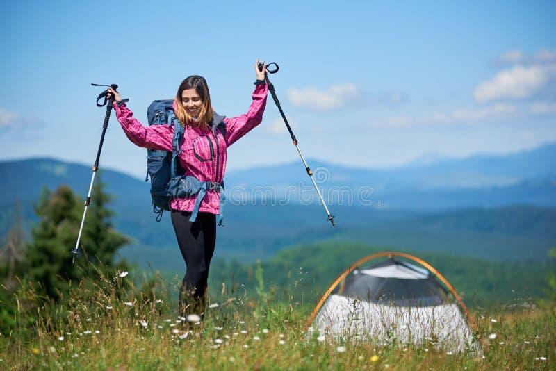 Kobieta turystyczny pobliski camping w górach z plecakiem i trekking wtyka w ranku zdjęcia stock