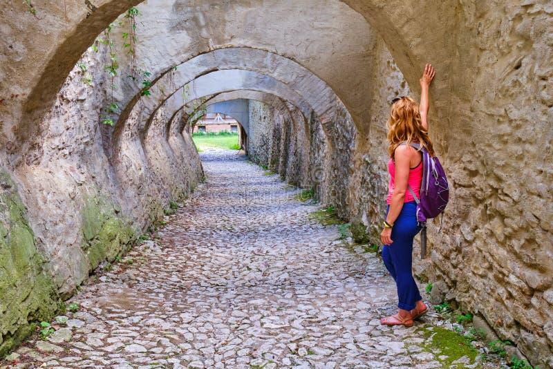 Kobieta turystyczny przyglądający rzut archway z wielokrotność łukami, brukującymi z brukowem, w Biertan fortyfikował kościół, Tr obrazy royalty free