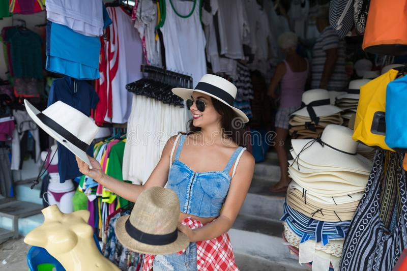 Kobieta Turystyczny Wybiera kapelusz Na Azjatyckim Ulicznym rynku Odzieżowy Młody Żeński zakupy Na wakacje fotografia stock