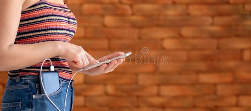 Kobieta używa mądrze telefon podczas gdy ładować na władza banku fotografia royalty free