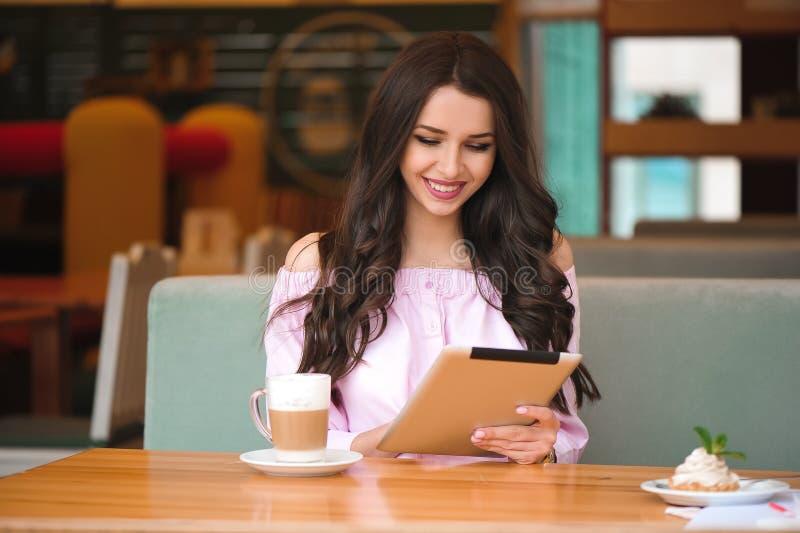 Kobieta używa pastylka w sklepie z kawą fotografia royalty free