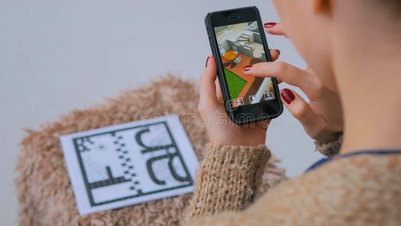 Kobieta używa smartphone z zwiększającą rzeczywistością app, sprawdza wirtualnego domowego plan zdjęcie stock