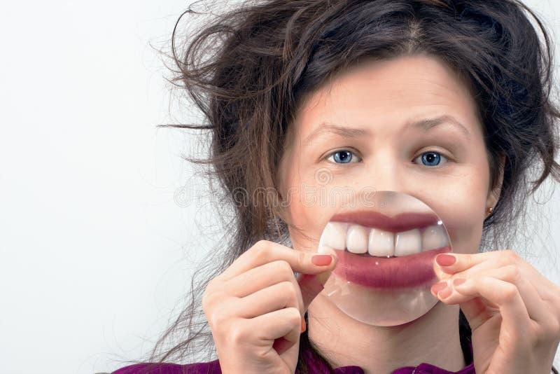 Kobieta uśmiech przez powiększać - szkło zdjęcie royalty free