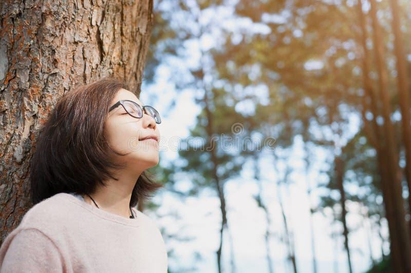 Kobieta uśmiecha się świeże powietrze i oddycha przy sosnowym lasem z sunlig zdjęcie stock