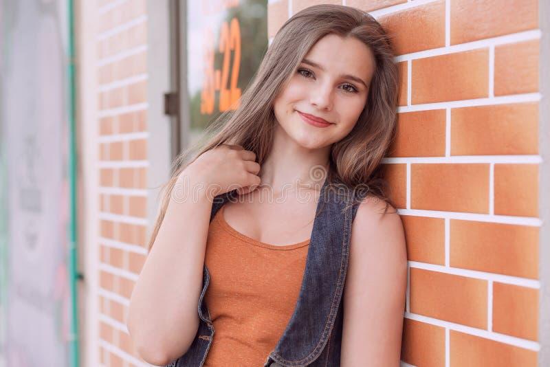Kobieta uśmiecha się outdoors pomarańcze niebieskich dżinsów miedzianą koszulową kurtkę zdjęcia stock