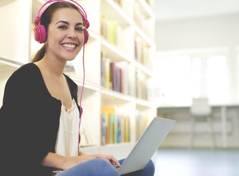 Kobieta uśmiechnięci jest ubranym różowi hełmofony w bibliotece fotografia stock