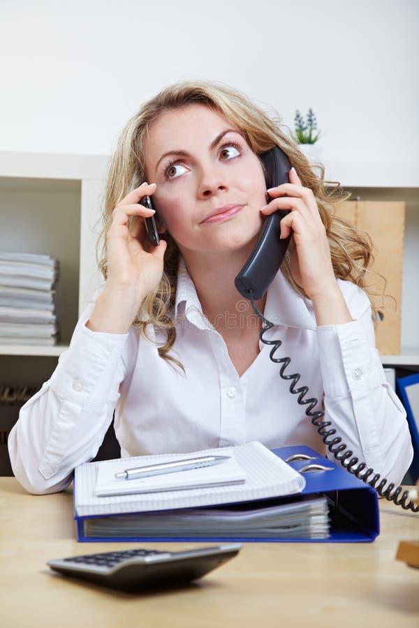 Kobieta używać dwa telefonu obrazy royalty free