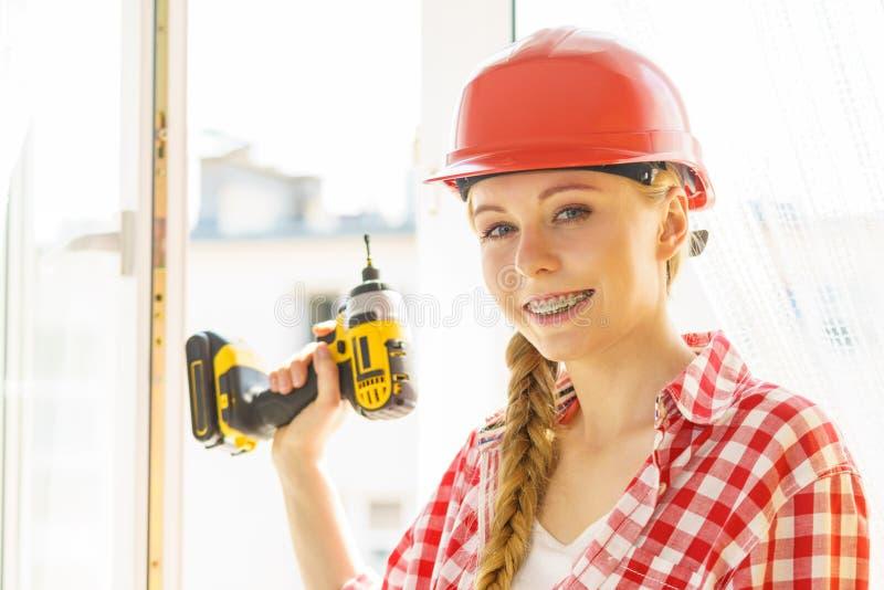 Kobieta używa świder załatwiać lub instalujący okno obrazy royalty free