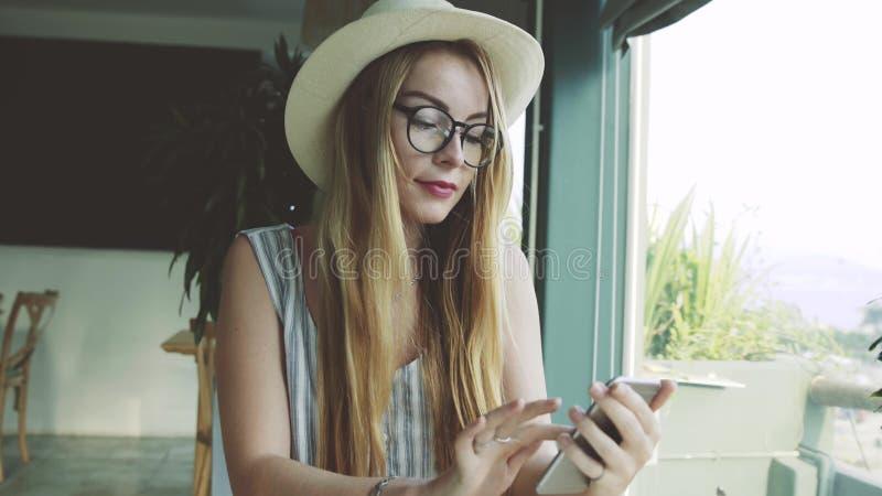 Kobieta używa app na smartphone w kawiarni pić kawowy i uśmiechnięty zdjęcia stock