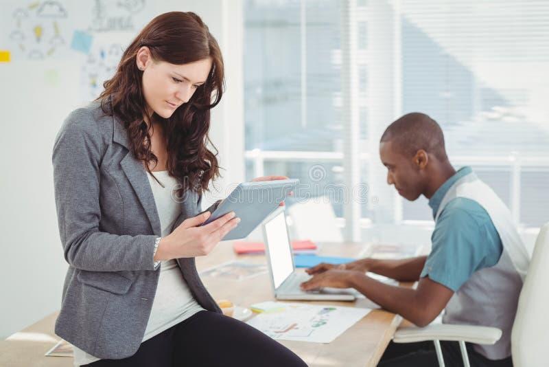 Kobieta używa cyfrową pastylkę podczas gdy siedzący na biurku z mężczyzna działaniem zdjęcia royalty free