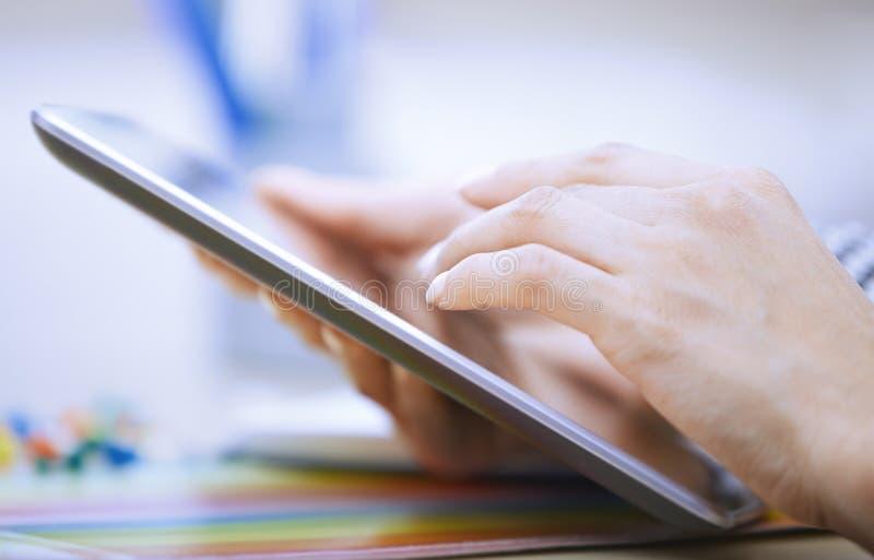 Kobieta używa cyfrową pastylkę przy biurem obraz stock