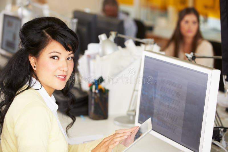 Kobieta Używa Cyfrowej pastylkę W Ruchliwie Kreatywnie biurze obraz royalty free
