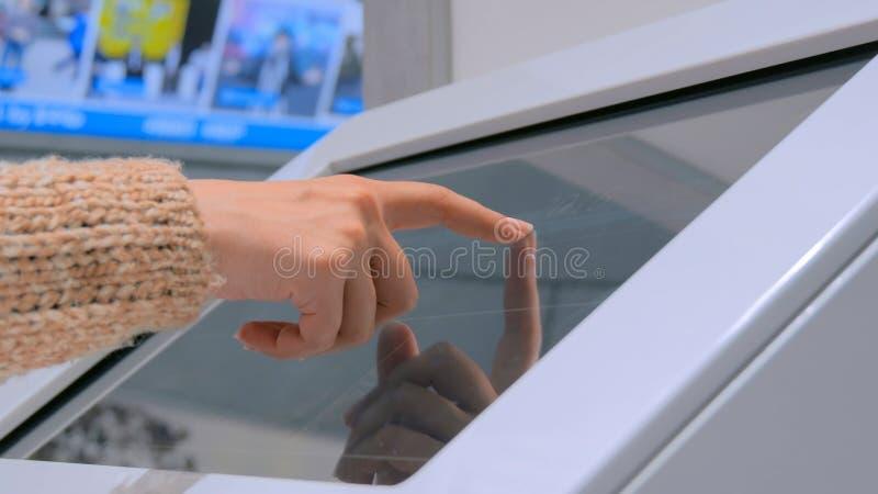 Kobieta używa interaktywnego ekranu sensorowego pokazu przy miastową wystawą fotografia royalty free