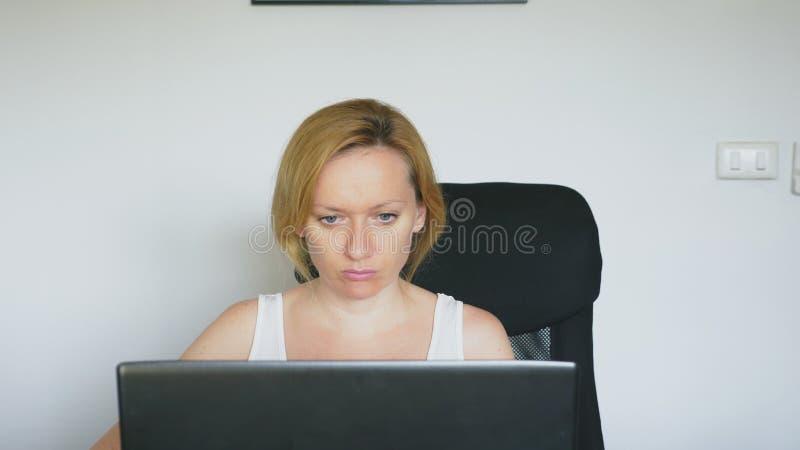 Kobieta używa jej laptop, siedzi przy stołem, gniewny i podrażniony, przysięga ludzkie emocje Internetowy nałogu pojęcie fotografia stock