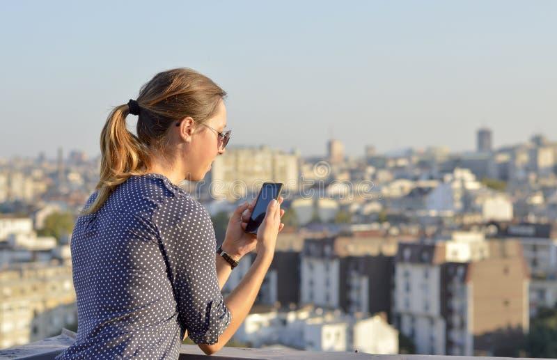 Kobieta używa jej smartphone na dachu obrazy stock