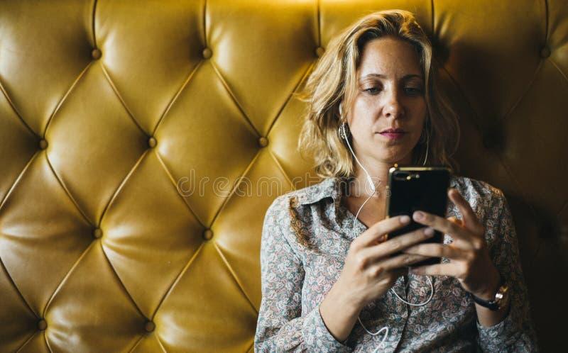 Kobieta używa jej telefon słucha muzyka obrazy royalty free