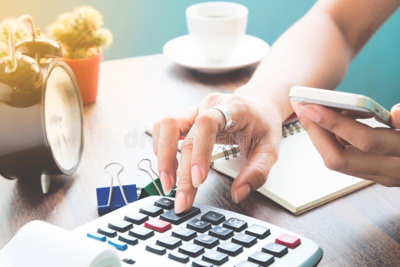 Kobieta używa kalkulatora i weryfikuje mobilną bankowość na smartphone zdjęcia stock