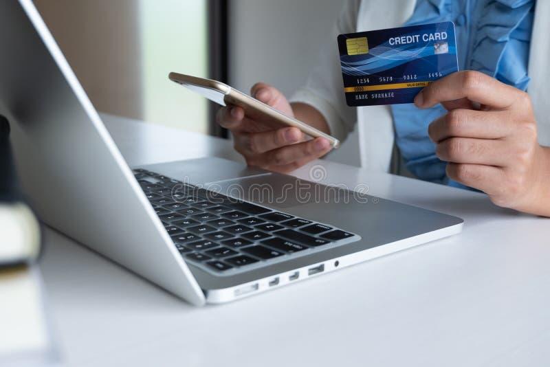 Kobieta używa kartę kredytową dla online zakupy na jej telefonie i laptopie zdjęcia stock