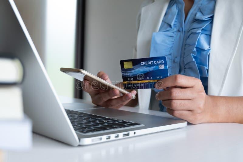 Kobieta używa kartę kredytową dla online zakupy na jej telefonie i laptopie zdjęcie stock